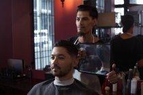 L'uomo che guarda i suoi nuovi capelli tagliati allo specchio dal barbiere — Foto stock
