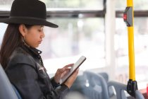 Teenage girl using digital tablet in the bus — Stock Photo