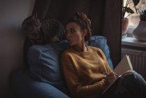 Женщина дуется на своего домашнего кота во время записи в дневнике дома — стоковое фото