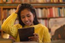 Девочка-подросток, с использованием цифрового планшета в библиотеке — стоковое фото
