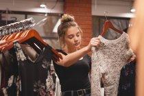 Bella ragazza che seleziona i vestiti da rack nel centro commerciale — Foto stock