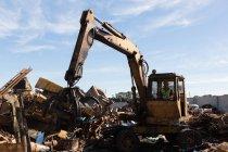 Crane lifting scrap metal in the junkyard — Stock Photo