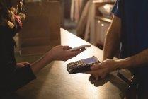Mädchen bezahlt mit Handy am Schalter — Stockfoto