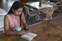Adolescente à l'aide de téléphone portable dans le restaurant — Photo de stock