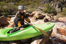 Femme accroupie avec bateau kayak sur les rochers au bord de rivière. — Photo de stock