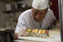 Senior chef preparing sushi in kitchen at hotel — Stock Photo