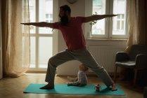 Человек, выполняющий йогу на коврике для упражнений дома — стоковое фото