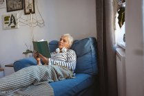 Senior woman relaxing on a sofa reading a book in living room at home — Stock Photo