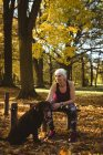 Thoughtful senior woman in a park with her dog on a sunny day — Stock Photo