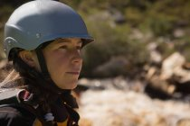 Portrait of female kayaker in protective helmet by river. — Stock Photo