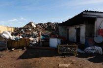 Montón de basura en el depósito de chatarra en un día soleado - foto de stock