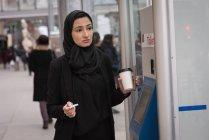 Mulher de hijab, segurando o copo descartável na estação ferroviária — Fotografia de Stock
