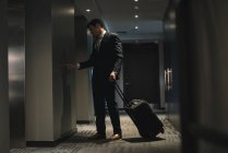 Businessman with trolley bag waiting for lift in hotel — Stock Photo