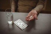 Sección media de una mujer mayor con tabletas y un vaso de agua - foto de stock
