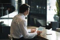 Продуманий бізнесмен, використовуючи цифровий планшетний в офісі лобі — стокове фото
