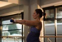 Donna incinta che si allena con i manubri a casa — Foto stock