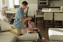 Jeune fille à l'aide d'une tablette numérique tout en peignant ses cheveux à la maison de père — Photo de stock