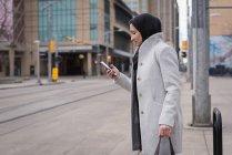 Donna in hijab utilizzando il telefono cellulare sulla strada della città — Foto stock