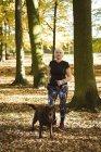 Mulher sênior andando no parque com um cachorro em um dia ensolarado — Fotografia de Stock