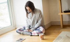 Jeune femme utilisant un téléphone portable sur le sol à la maison . — Photo de stock