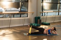 Woman exercising with resistance band at home — Stock Photo