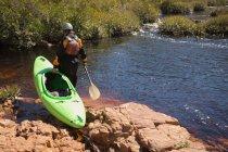 Femme qui marche avec kayak bateau et pagayer à rivière. — Photo de stock