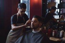 Uomo che si fa tagliare i capelli con la forbice dal barbiere — Foto stock
