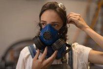 Artisanat féminin portant un masque à gaz en atelier . — Photo de stock