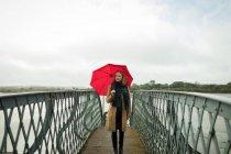 Junge Frau mit Regenschirm am Bahnhof — Stockfoto