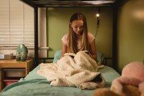 Девочка читает книгу, сидя на кровати в спальне дома . — стоковое фото