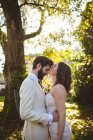 Bride kissing on grooms forehead in the garden on a sunny day — Stock Photo
