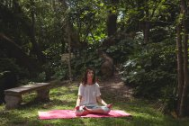 Mulher praticando ioga no jardim em um dia ensolarado — Fotografia de Stock