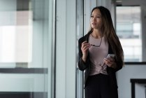 Asian businesswoman looking away while using her mobile phone in the lobby — Stock Photo