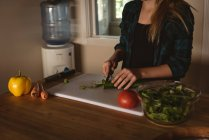 Mid section of girl standing in kitchen and cutting vegetables with knife at home. — Stock Photo