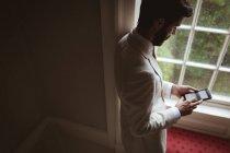 Высокий угол обзора жениха с помощью мобильного телефона возле окна — стоковое фото