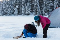 Couple preparing bonfire near tent in snowy woodland during winter. — Stock Photo