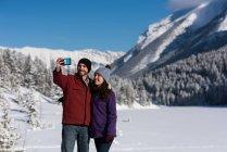 Селф принимая пару с мобильным телефоном в снежные горы. — стоковое фото