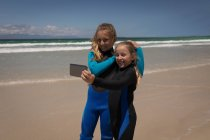 Happy siblings in wetsuit taking selfie with mobile phone on beach — Stock Photo