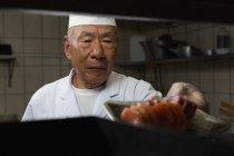 Старший шеф-повар готовит суши в кухне отеля — стоковое фото