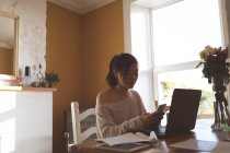 Woman using mobile phone while working on laptop at home — Stock Photo