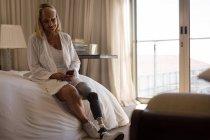 Зрелая женщина с протез, используя мобильный телефон в спальне дома. — стоковое фото