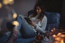 Женщина читает роман рядом с зажженными свечами, чаем и миской клубники дома — стоковое фото
