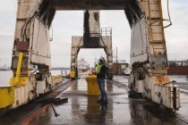 Dock worker inspecting the huge cranes in shipyard — Stock Photo