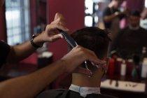 Uomo che ottiene i suoi capelli tagliati con trimmer al negozio di barbiere — Foto stock