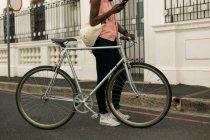 Femme avec vélo utilisant le téléphone portable dans la rue de la ville — Photo de stock