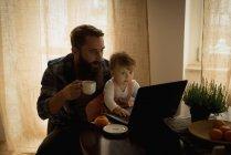Отец пьет кофе, а сын играет дома на ноутбуке. — стоковое фото