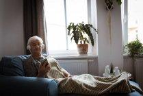 Пожилая женщина слушает музыку в наушниках, пользуясь мобильным телефоном в гостиной — стоковое фото