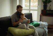 Père et fils utilisant une tablette numérique à la maison — Photo de stock