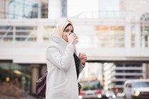 Donna in hijab bere caffè sulla strada della città — Foto stock