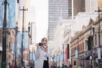 Mulher em hijab clicando em fotos com câmera digital na rua da cidade — Fotografia de Stock
